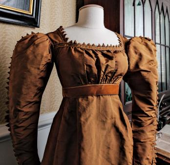 """Ribbed silk taffeta dress with satin trim and modern ribbon waistband Note: Zig-zag elements were named (and misspelled) """"vandykes"""" after Anthony Van Dyck, the Flemish portrait painter whose subjects often wore lace collars with similarly shaped edges."""