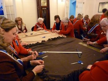 The National Board of Management worked together together to tie the edges of the fleece blankets for the Veterans