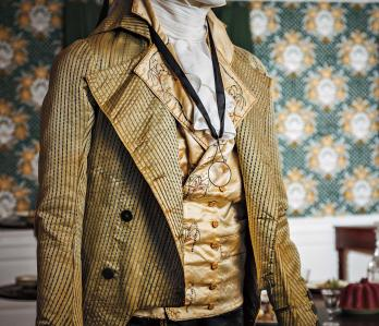 """Green striped silk coat over a silk satin embroidered waistcoat believed to be the wedding waistcoat of Thomas Rumrill in 1795. The brass monocle or """"quizzing glass"""" was possibly owned by Major Joseph Savage."""