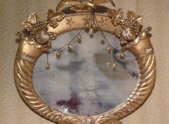 This decorative mirror with an eagle detail can be found in the Alabama Period Room